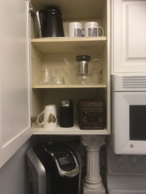 This is where we keep everything to do with tea and coffee, in the cupboard above the Keurig. We like to use the refillable pods for two reasons: it saves us money because we buy our coffee in large tins, and because refilling them saves the environment. Top shelf: mugs and the carafe to the Keurig. Middle shelf: Glass teapot with candle warmer, sugar bowl and cream jug. Bottom shelf: More mugs, milk frother for our morning lattes, Keurig pods in basket.